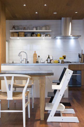 大理石調の壁面、白い石貼りのカウンター、メタルの天板のテーブル...。素材のミックス感がいい。