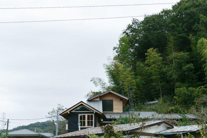 """裏山を背景に、住まいと""""お菓子小屋""""が並ぶ。にほんの里100選に選ばれている里山が近く、野うさぎを見かけることもあるそうだ。"""