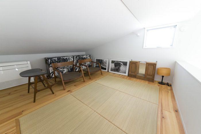 畳を敷いたロフトは昼寝にぴったり。村澤一晃さんのチェアや、古道具のテーブルが、和を取り入れた空間になじむ。