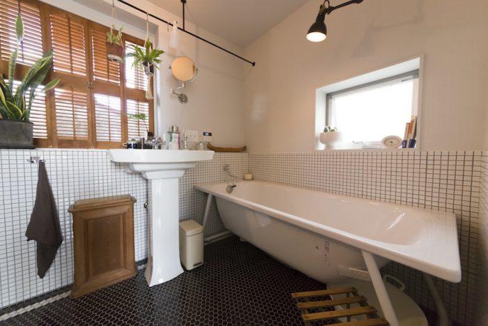 こだわりのバスルーム。物干しにもなるアイアンのバーは、階段の手すりやカーテンレールなどと合わせて友人の造形作家・関田考将さんにオーダーしたもの。