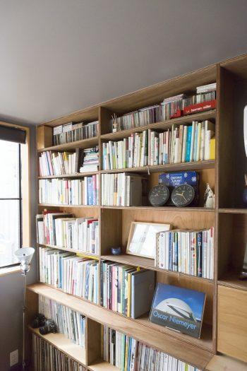 本棚は棚板の高さまで考えて造作。右下の蓋をあけるとライティングデスクとしても使える。