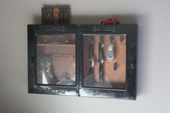ベッドサイドに掛けた時計・メガネのケースは、NYの床屋で使われていた古道具。ネットで落札。