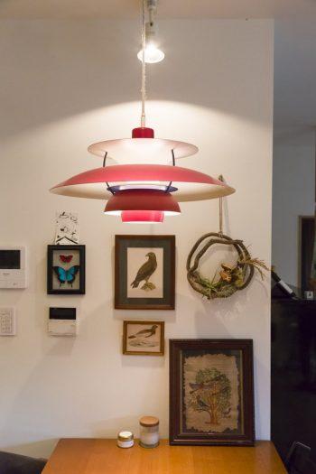 食卓テーブルをポール・ヘニングセンのペンダントライトが照らす。壁のリースはBEAMSで行うワークショップのために制作。