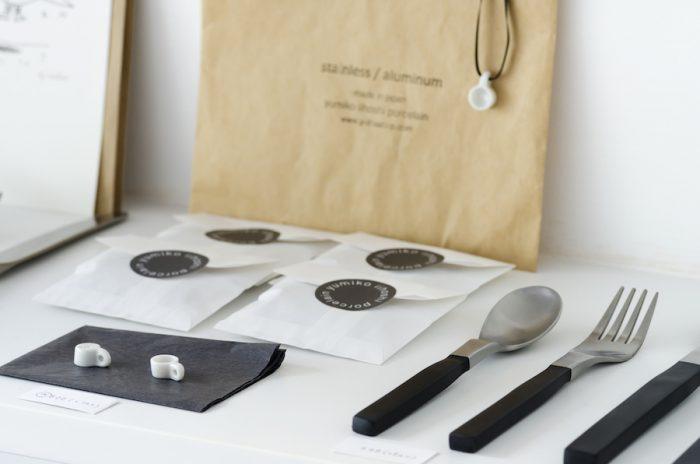 「yumiko iihoshi porcelain」の器に合うカトラリーをセレクト。買いやすい価格、使いやすいサイズ感でさまざまな種類がラインナップ。横にあるのは小さなマグカップの形をした磁器のチャーム。