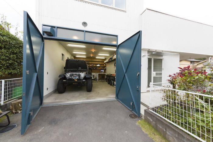 旗竿敷地の奥に建つ。大きな鉄扉の奥は、天井の高い広々としたガレージ。
