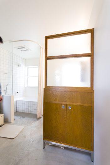 造作した棚は、トイレとバスルーム入り口の仕切りにもなっている。