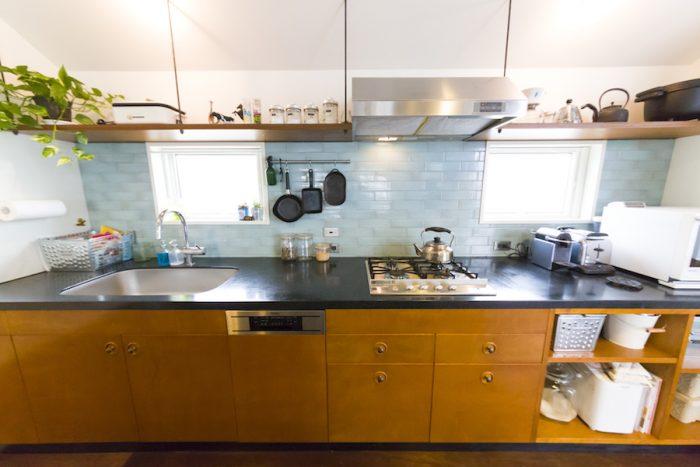 うすい青緑色のタイルがアクセント。キッチン台はHOUSETRAD の家具を造作。平賀さんの出身の、岩手の南部鉄器が映える。