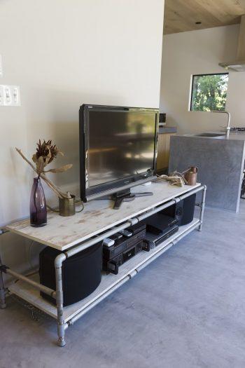 TV台はガス管を繋いで製作した直樹さんのDIY。「前の家に住んでいた時のものですが、置いてみたら横幅が壁にピッタリでした」
