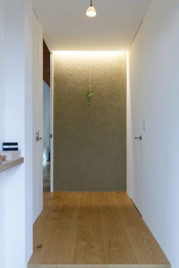 玄関を入って正面は、左官壁。風合いのある壁が、訪れる人を迎える。