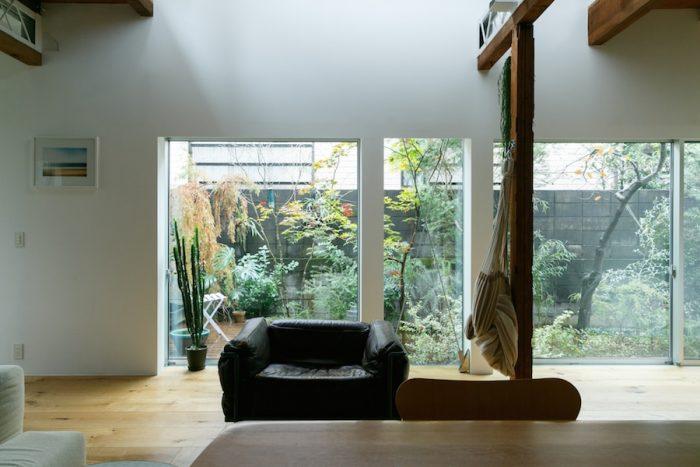 玄関ホールの扉の向こうには、明るく開放的なLDKが広がる。造園はen landscape designに依頼。ティーツリーなどオーストラリアの植物と、楓など日本の植物をミックスすることで、無国籍な雰囲気に。