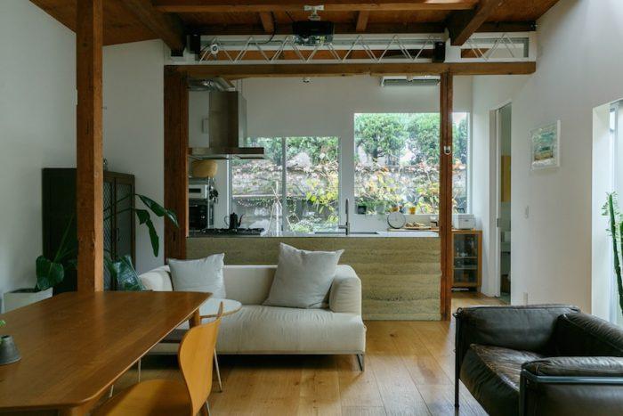 リビングからキッチンを見る。キッチンの背面にも開口部があり、外は物干スペースとして利用している。版築のキッチンが空間に表情を添える。右手のこげ茶の一人掛けのソファは、コルビジェのLC3。アイボリー色のソファはB&Bのもの。