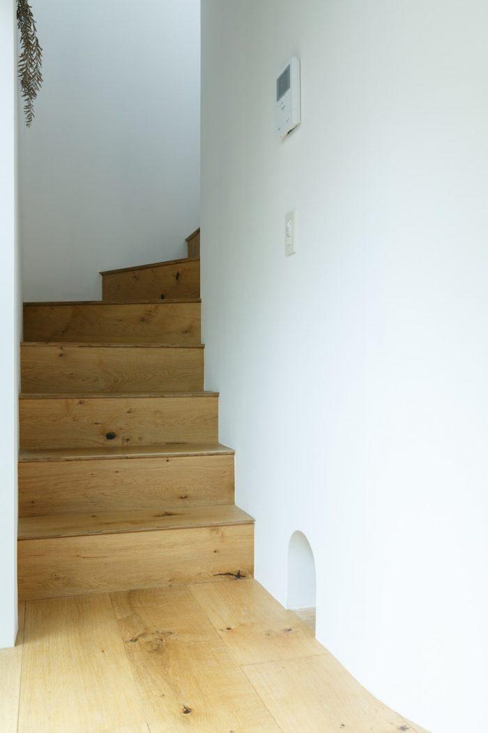 2階に向かう階段。1階床と階段には、うづくり仕上げのオーク材を用いた。幅が250ミリあるため、空間を広く見せる効果がある。右手のアールの開口部はかつて飼っていた猫のための通路。