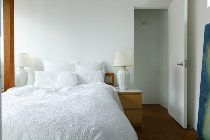 階段を上がったところは寝室。1、2階ともに、白い壁は自分達でペンキを塗った。「反射光をねらって、いちばん明るい白を選んで塗っています」。2階の床には構造合板を使うことで、構造面で強度を確保している。