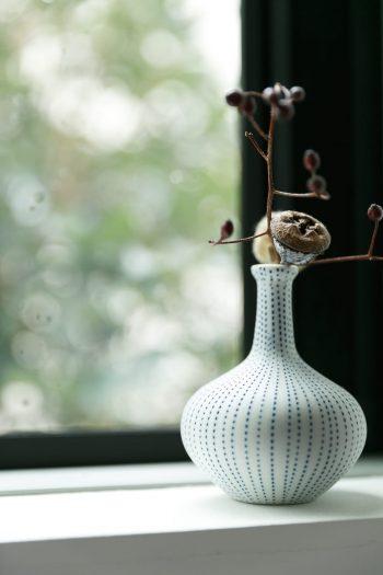 夫妻ともに植物を育てるのが好きだという。階段の窓辺にもさりげなく植物が活けられていた。