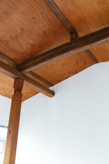既存建物の梁や柱がよくわかる2階の天井部分。木部は水洗いした上に、セルフビルドで柿渋を塗った。「コスト削減で取り組んだセルフビルドでしたが、貴重な経験になりました」。