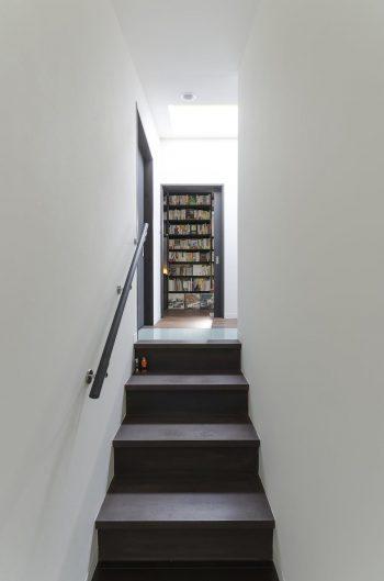 階からスキップで上った正面が書斎。右に折れると寝室がある。ガラスの床が1階まで光を落とす。