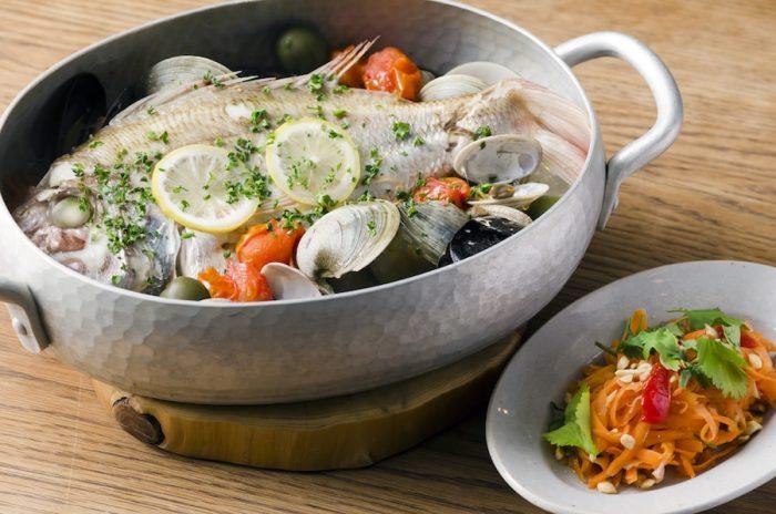 大きな魚一尾が丸ごと入った人気メニュー「いまの魚のアクアパッツァ」は魚介の旨味を堪能できる。3,400円。青パパイヤの替わりに、にんじんをたっぷり使った「にんじんのソムタム」。380円。