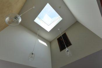 トップライトからリビングへと光が落ちる。壁の開口は佐藤さんの趣味の部屋に開けられた小窓。