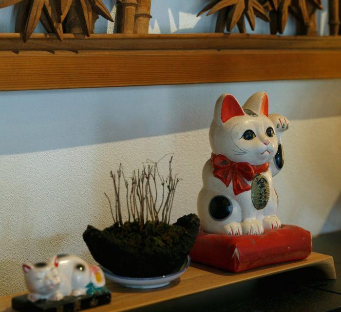 「猫の巣」の名にちなんで、あちこちに猫の置物がならぶ。写真右の招き猫は、その昔「ヒゲタしょうゆ」のノベルティとしてつくられた貯金箱。
