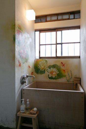 浴槽は、なんとヒノキ風呂。長風呂しながら本を読むのが、トモさんの至福の時なのだそう。壁はトムさんが友人とともにペイントした。