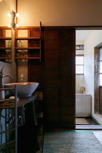 洗面室から浴室を見る。古民家の落ち着いた佇まいがありながらも、洗面ボウルや水栓のデザインに、外国人が暮らしていた頃の面影が感じられる。