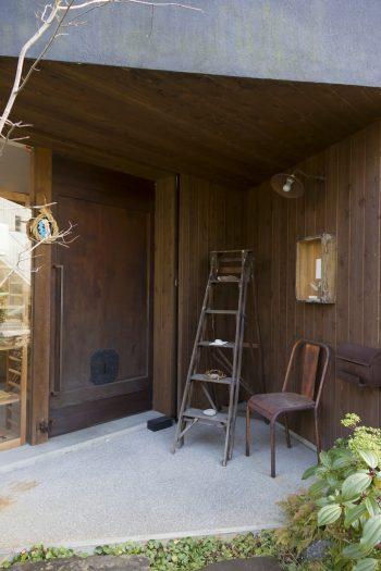 店舗の入り口は古民家で使われていた重厚なドアを設置。椅子やポストボックスが錆びて風合いを出している。