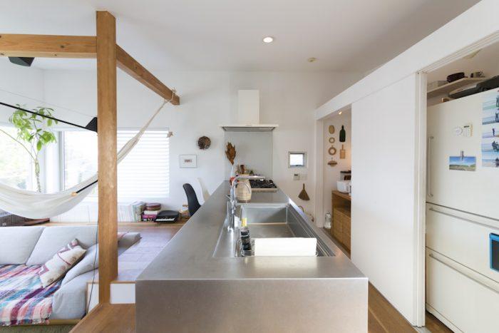 こだわりが詰まったシンプルなキッチン。扉を閉めれば、冷蔵庫や収納庫がすっきりと内蔵できる。ステンレスのキッチン台は図面を描いてオーダ―したもの。