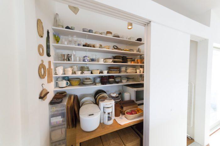 食器、調理器具、食材などすべてが収まるパントリーのような収納。扉だけを設けてもらい、後から棚をご主人とふたり、DIYで取り付けた。味わいのある器が並ぶ。
