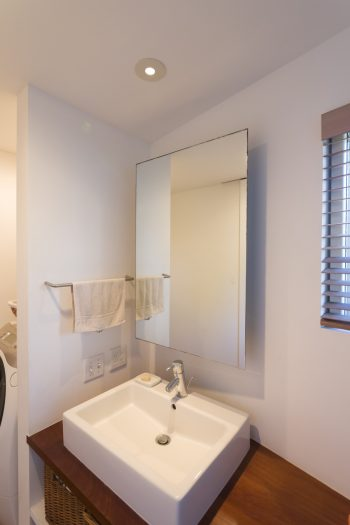 洗面台の鏡は、あえて後ろ側にある棚より大きいサイズに。開閉しやすく見た目にも美しい。