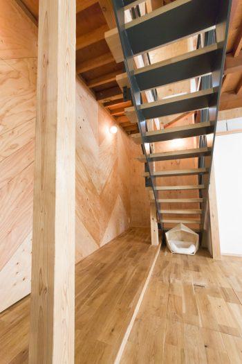 階段の横の壁は、合板をヘリンボーン柄に貼っている。「ドアの部分もヘリンボーンにしてあるこだわりが気に入っています」