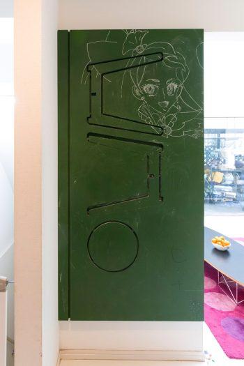 子どもの落書き用として設けた黒板塗装をした壁。壁面収納のスツールは久保さんの遊び心。壁から取り出して組み立てれば、実際に座ることができる。