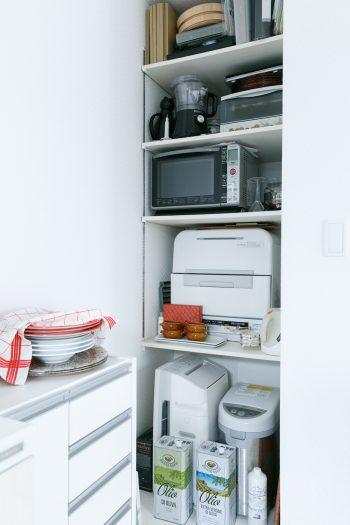 キッチン脇に棚を設け、電子レンジなどの調理機器をまとめて収納。ダイニング側からは視界に入らないため、キッチンがすっきり見える。