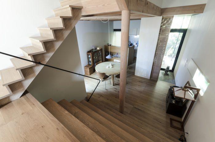 リビングのレベルから玄関とダイニング、キッチンを見る。幅の広い階段は、人が多く集まる食事会の時などにダイニングとリビングを分断せず、また腰かけることができるようにつくられた。