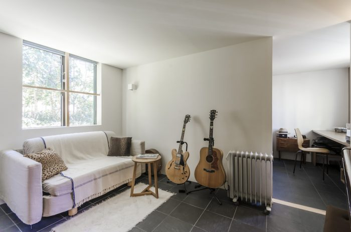 ギブソンのギターとピアノが置かれた地下の部屋は、とても落ち着けるためYさんお気に入りの空間。ソファでレコードを聴くのが好きという。地下も奥行き方向で部屋の大ききが変えられている。床にはこのレベルだけスレートが張られている。