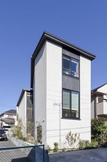 建物の右側と裏手に隣家が迫る敷地。棟をずらしてできた部分にスリット状の開口を設けている。