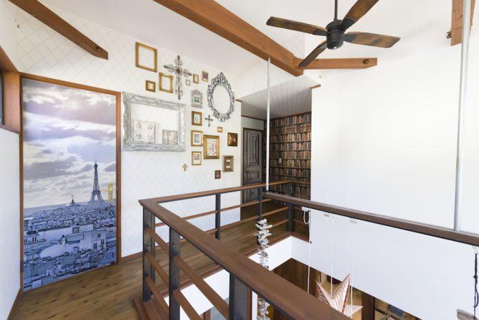 吹き抜けになった2階の廊下。ロンドンなどで買い集めていたアンティークのフレームを壁に。