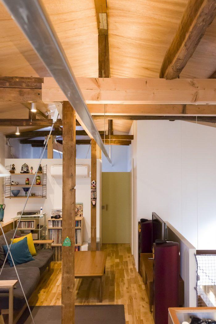 奥が寝室。壁を低くして天井を見せることで、広がりが感じられる。部屋をまっすぐに貫く間接照明のデザインもおもしろい。