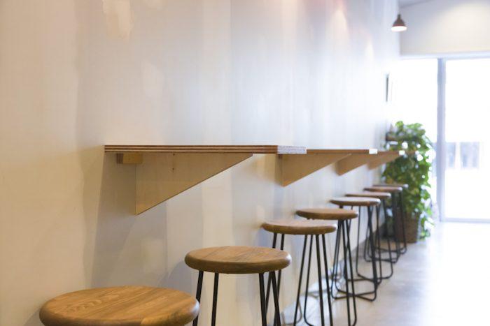 ミニマルな印象の、壁付けの小さなテーブルとスチールの脚のチェアが並ぶ。