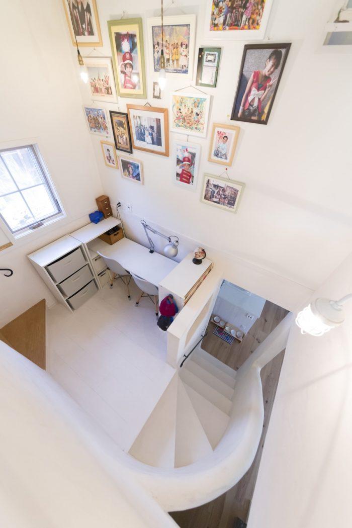 中二階の勉強スペース。板を載せただけのデスクは、子どもが巣立ったあとは簡単に撤去できる。丸みを帯びた階段が、リビングのやさしいアクセントに。