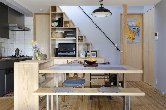 建具や家具の木の色と壁のグレーとの相性がとてもいい。階段下の収納は電子レンジなどが納まるように夫妻のリクエストでつくられたもの。