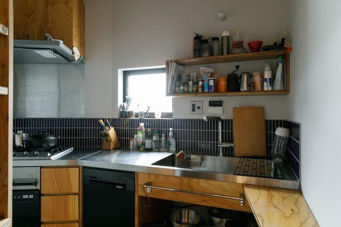 フルオーダーのキッチン。ステンレスとラーチ合板をベースに、青いタイルがアクセントになっている。