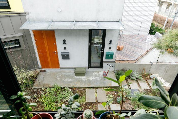 「Hutte Zenpukuzi」の2階から共用庭を見下ろす。右手のガラスドアがアトリエの入口、左手の木製ドアが里奈さんの親世帯の住居スペースにつづく。