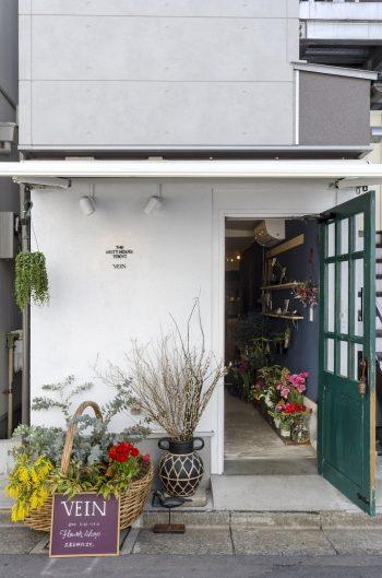 室内の壁だけでなく、外壁も自分たちの手で白く塗り直したという。店はモスグリーンの扉を目印に。