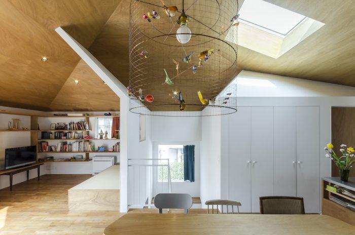 天窓から入った光が内部の白い屋根で反射して室内に広がる。左の本棚にはPR関係の仕事をされている奥さんのフランス文学の本やフランス映画のDVDなどが並ぶ。手前のランプシェードはフランスの作家もので「鑑賞できるもの」という趣旨から選んだもの。