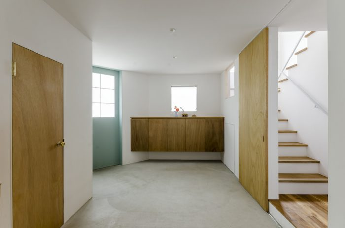 玄関を入った場所に広めにつくられた土間スペース。左に2匹の猫のためにつくられた部屋がある。