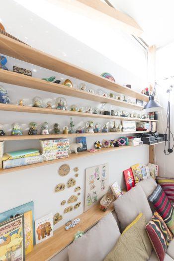 棚には旅先で買ったスノードームが並ぶ。「ソファの裏に子どもがオモチャを落とすので板でガードしました」。本を置けるちょっとしたスペースになっている。