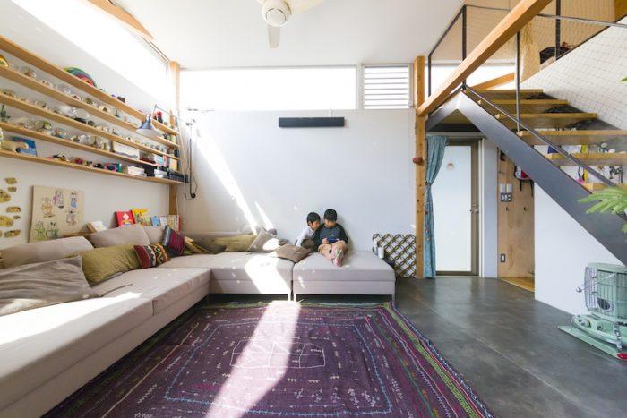 足を伸ばして座れる大型のソファはTime & Styleで購入。コンクリート打ち放しの床にラグを敷いて。