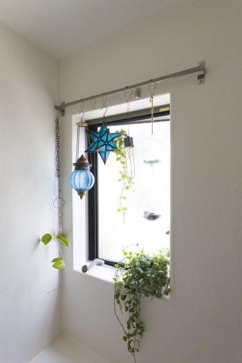 バスルームの窓には、ブルーのガラスとハンギングの植物を飾って。