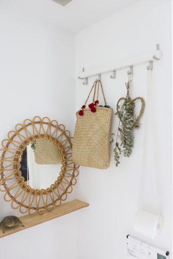 籐の鏡やユーカリを飾ったトイレの一角。トイレットペーパーホルダーはフックから下げられた紐。
