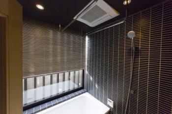 坪庭を眺めながら入浴できるバスルーム。蔵を意識した黒のタイルが斬新。